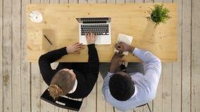 2 предпринимателя сидя совместно работать в столе офиса кладя примечания к тетради акции видеоматериалы