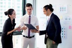 3 предпринимателя стоя в современном офисе смотря документ файла и говоря в конференц-зале Стоковые Изображения