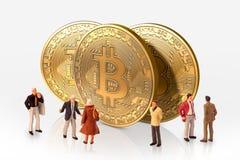 Представление группы людей рядом с bitcoins, изолированными на белой предпосылке Стоковая Фотография