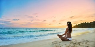 Представление лотоса женщины практикуя на пляж стоковое фото rf