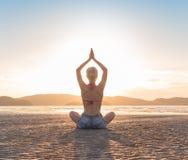 Представление лотоса маленькой девочки сидя на пляж на заходе солнца, взморье раздумья летних каникулов йоги красивой женщины пра стоковые фото