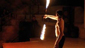 Представление шоу огня на этапе Танцы молодого человека с пламенистыми вентиляторами на шоу ночи ( сток-видео
