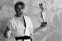 Представления Гая в белое кимоно показывая кулак держат золотой приз Человек с одичалой стороной на красочной предпосылке Самолет Стоковые Изображения RF