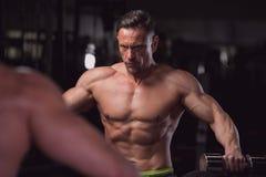 Представлять мышечного фитнеса модельный без рубашки в спортзале Стоковое Изображение RF