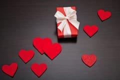 Представьте на день ` s валентинки, будьте матерью дня ` s или свадьбы, обернутых в красной бумаге, белом смычке и красных сердца Стоковое Изображение RF