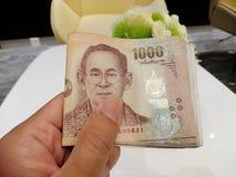 Представьте тайские банкноты для оплаты - банкноту 1000 тайцев бата в руке, короле Rama 9 на тайских деньгах стоковые фото