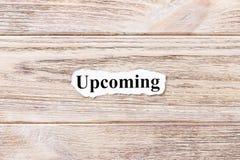 Предстоящий слова на бумаге Концепция Слова предстоящего на деревянной предпосылке стоковое фото rf