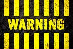Предупредительный знак при желтые и черные нашивки покрашенные над треснутой предпосылкой текстуры бетонной стены грубой Стоковое Фото