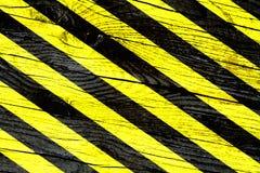Предупредительный знак при желтые и черные нашивки покрашенные над треснутой деревянной поверхностной предпосылкой текстуры Стоковые Фотографии RF
