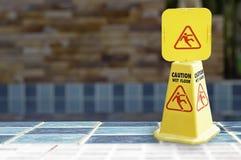 Предупреждающие плиты намочили пол около бассейна сделанного из желтой пластмассы стоковое фото rf