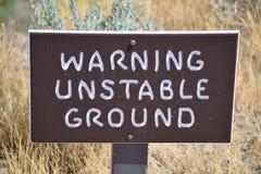 Предупреждающий неустойчивый земной знак на голове следа Стоковая Фотография RF