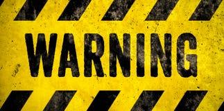 ПРЕДУПРЕЖДАЯ текст слова знака опасности как восковка с желтыми и черными нашивками покрашенными над предпосылкой текстуры цемент стоковые фотографии rf