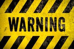 ПРЕДУПРЕЖДАЯ текст слова знака опасности как восковка с желтыми и черными нашивками покрашенными над предпосылкой текстуры цемент стоковая фотография