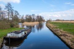 Предыдущий взгляд весны на Giethoorn, Нидерланд, традиционной голландской деревне с каналами Типичная низкая шлюпка вдоль лужайки стоковые изображения rf