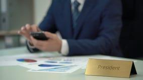 Президент корпорации работая с диаграммами инвестиционного проекта, используя устройство видеоматериал