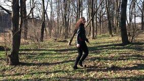 Прекрасная девушка в бегах черных кожаной куртки через древесины и освобождаясь улыбки красиво и поворотах к камере акции видеоматериалы