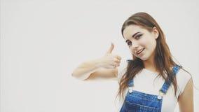 Прекрасная девушка смотря камеру отскакивая joefully и подмигивая на камере указывая ее большой палец руки вверх Женщина волнисты сток-видео