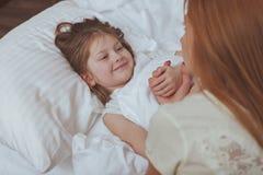 Прекрасная женщина наблюдая ее спать дочери стоковая фотография rf
