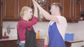 Прекрасная молодая женщина и мужчина в апранах снимают перчатки и поднимают пятерых. Семья заканчивает уборку дома акции видеоматериалы