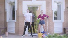 Прекрасная молодая женщина и мужчина танцуют на крыльце дома Пара убирает дом вместе Счастливой рутины сток-видео