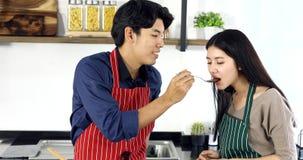 Прекрасные азиатские пары в кухне, они имеют еду сток-видео