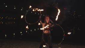 Прекрасные женщины закручивая обручи hula огня на береге реки