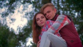 Прекрасные люди в любов обнимающ и наслаждающся моментом совместно, предпосылкой природы и расслабленными жизнерадостными парами видеоматериал
