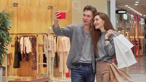 Прекрасные молодые пары принимая selfies пока ходящ по магазинам на торговом центре совместно акции видеоматериалы
