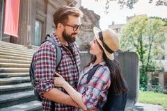 Прекрасные пары стоят на лестницах и обнимают один другого Они смотрят и усмехаются Туристы имеют rocksacks Beautfiul солнечное стоковые изображения rf