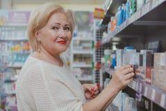 Прекрасные старшие покупки женщины на аптеке стоковые изображения rf