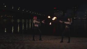 Прекрасные firegirls выполняя волшебное шоу с пламенем