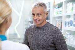 Прекрасный женский аптекарь помогая ее клиенту стоковые изображения rf