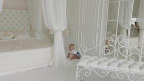 Прекрасный счастливый мальчик играет в белой комнате акции видеоматериалы