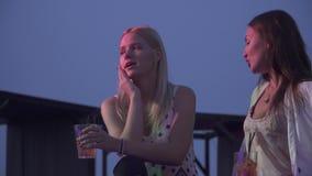 2 прекрасных девушки выпивая коктейли в ночном клубе Девушки сидят с коктейлями и беседуют на лете видеоматериал