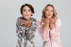 2 прекрасных девушки нося пижамы изолированные над серым цветом стоковые изображения rf
