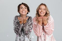2 прекрасных девушки нося пижамы изолированные над серым цветом стоковая фотография rf