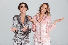 2 прекрасных девушки нося пижамы изолированные над серым цветом стоковая фотография