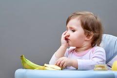 Прелестная девушка малыша имеет потеху пока еда некоторого приносить на сероватой предпосылке Стоковые Изображения
