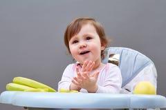 Прелестная девушка малыша имеет потеху пока еда некоторого приносить на сероватой предпосылке Стоковые Фотографии RF