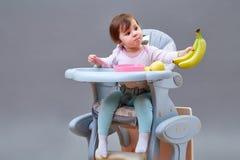 Прелестная девушка малыша имеет потеху пока еда некоторого приносить на сероватой предпосылке Стоковая Фотография RF