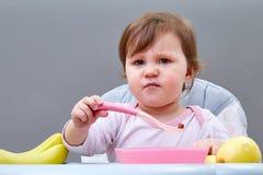 Прелестная девушка малыша имеет потеху пока еда некоторого приносить на сероватой предпосылке Стоковые Фото