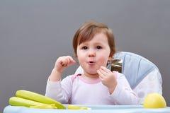 Прелестная девушка малыша имеет потеху пока еда некоторого приносить на сероватой предпосылке Стоковая Фотография