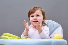 Прелестная девушка малыша имеет потеху пока еда некоторого приносить на сероватой предпосылке Стоковое фото RF