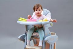 Прелестная девушка малыша имеет потеху пока ел на сероватой предпосылке Стоковая Фотография