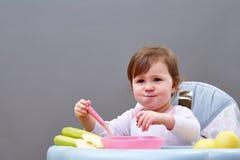 Прелестная девушка малыша имеет потеху пока ел на сероватой предпосылке Стоковые Фото