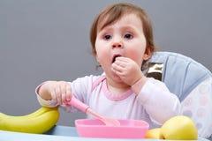 Прелестная девушка малыша имеет потеху пока ел на сероватой предпосылке Стоковое Фото