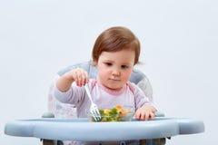 Прелестная девушка малыша имеет потеху пока ел потушенные овощи на белой предпосылке Стоковое фото RF