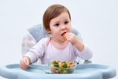 Прелестная девушка малыша имеет потеху пока ел потушенные овощи на белой предпосылке Стоковые Фото