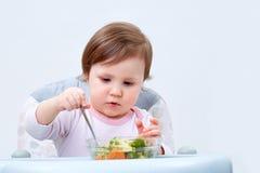 Прелестная девушка малыша имеет потеху пока ел потушенные овощи на белой предпосылке Стоковые Фотографии RF