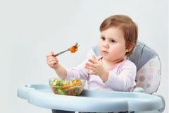 Прелестная девушка малыша имеет потеху пока ел потушенные овощи на белой предпосылке Стоковое Изображение RF